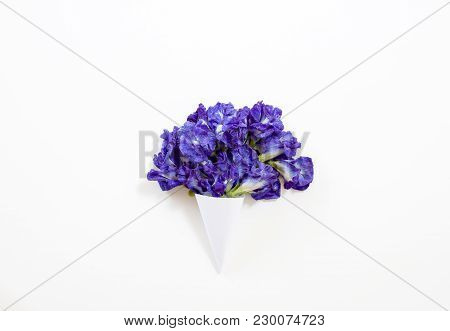 Paper Cone With Butterfly Pea Or Blue Pea Bouquet On White Background. flat Lay, Top View
