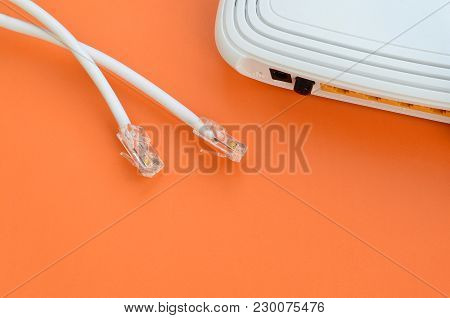 Internet Router And Internet Cable Plugs Lie On A Bright Orange Background. Items Required For Inter