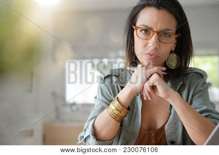 Brunette girl with eyeglasses looking at camera with skeptic look
