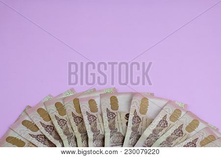 Thai Hundred Baht Banknotes On Pink Background.