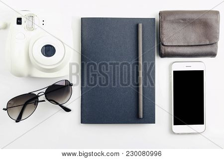 Flat Lay Of Black Notebook, Sunglass, Wallet And Camera On White Background With Vintage filter. Top