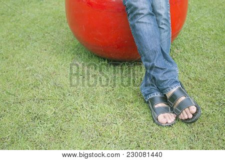 Man Sitting On Ceramic Ball Chair In The Park.