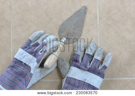 Towel And Construction Gloves On The Floor. Top View.