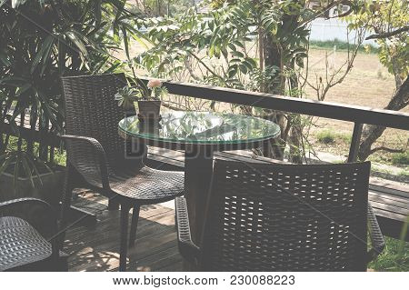 Round Wood Table On Terrace Of House. Wicker Rattan Chair On Patio Near Garden At Home. Relax Lifest