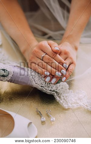 Female Hands Of The Bride With A Beautiful Blue Manicure, Ring On The Finger. Veil With Lace Next To