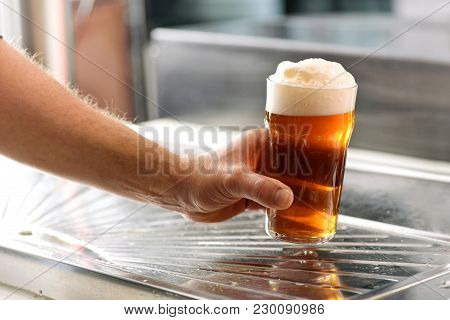 Man Holding A Fresh Glass Of Chilled Draft Beer