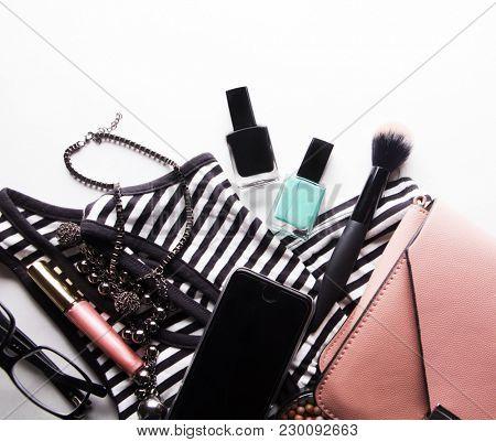 Stylized feminine flatlay with glasses, foundation, lip gloss, powder, brush, handbag, striped shirt poster