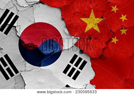 Flag Of South Korea And China Painted On Cracked Wall