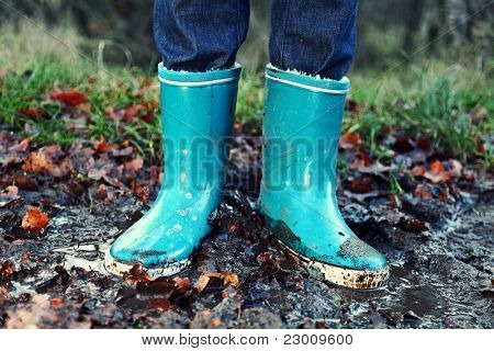 Fall / Autumn concept - Rain boots in mud puddle. Blue woman rain boots outdoors in action.