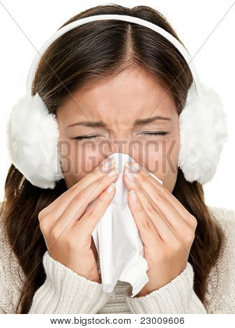 Flu or cold - sneezing woman sick blowing nose. Young woman being cold wearing earmuffs and sweater. Asian Caucasian female model.