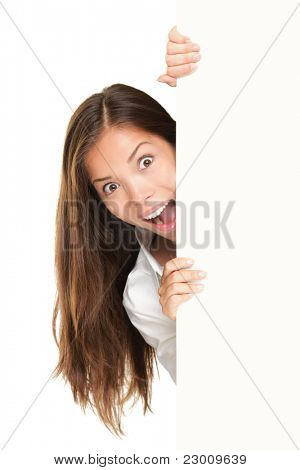 Sign people - woman peeking out from behind billboard paper poster. Excited woman looking surprised. Beautiful brunette with long hair. Asian Caucasian female model isolated on white background
