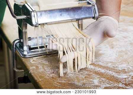 Process Of Production Of  Pasta. Fresh Pasta And Pasta Machine On Kitchen Table