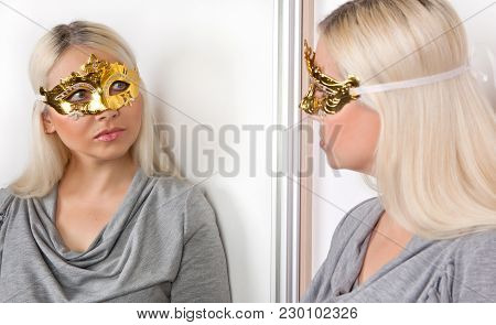 A Woman In A Carnival Gold Mask With Glasses Looks Thoughtfully At Her Reflection In The Mirror.