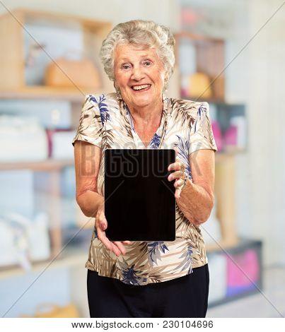 Portrait Of A Senior Woman Holding A Digital Tablet, Indoor