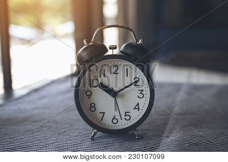 Closeup Image Of A Black Alarm Clock On The Table With Blur Background