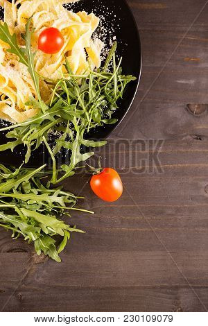 Top View Of Plate With Pasta Next To Greenery And Cherry Tomatoes. Copyspace Available
