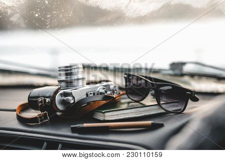 Notebook, Glasses And Film Camera On The Dashboard In The Car. Closeup Shot