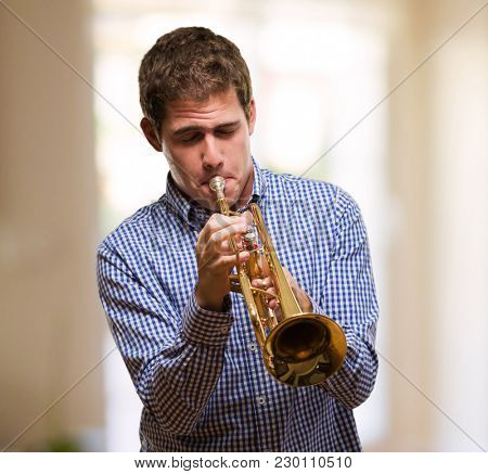 Handsome Man Blowing Trumpet against an abstract background