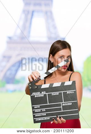 Woman In A Red Dress Holding Clapper Board at paris