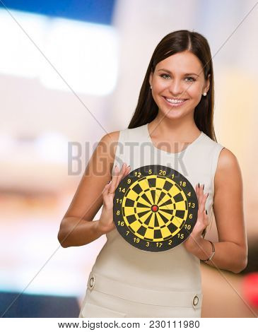 Portrait Of A Young Woman Holding Bull's Eye Smiling, indoor