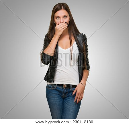 Portrait Of Surprised Young Woman against a grey background