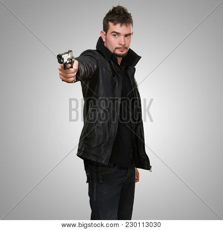handsome man pointing with gun against a grey background