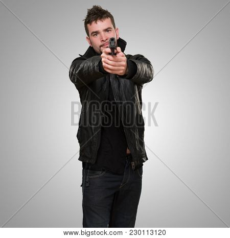 portrait of a man pointing with a gun against a grey background