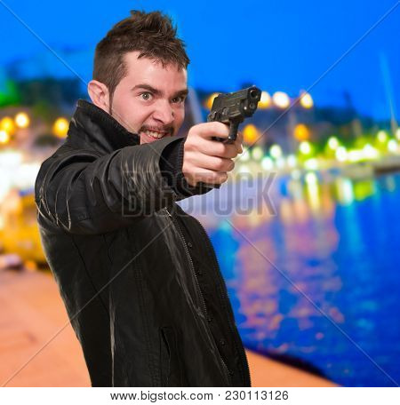angry man pointing with gun at a port by night