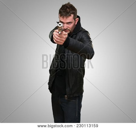 young man pointing with gun against a grey background