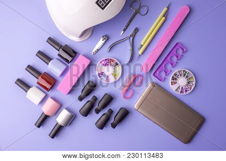 Set Of Cosmetic Tools For Manicure And Pedicure On A Purple Background. Gel Polishes, Nail Files And