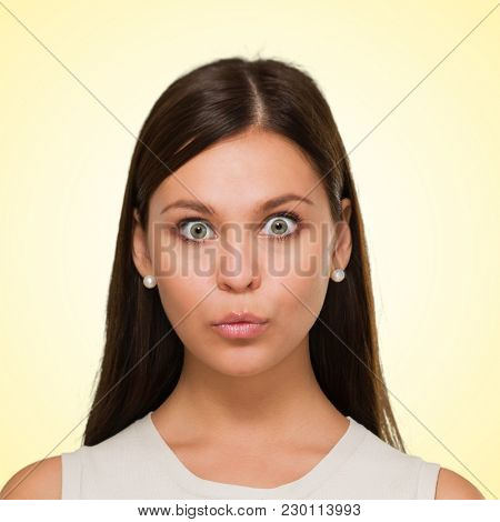 Surprised woman against a yellow background