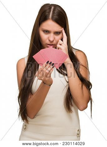 Confused Young Woman Holding Playing Cards On White Background