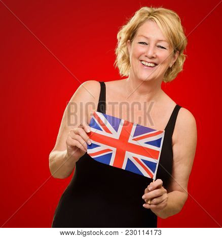 Happy Mature Woman Holding British Flag Isolated On Red Background