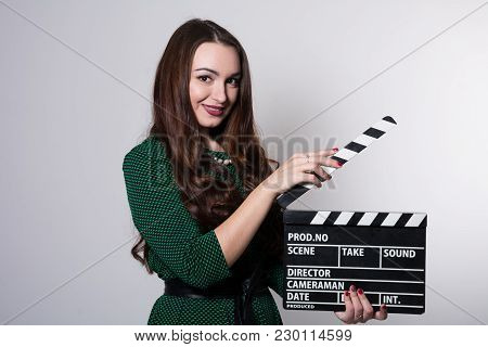 Smiling Young Woman Holding A Movie Clapper