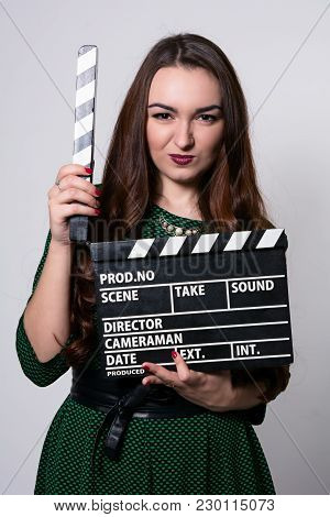Frowning Young Woman Holding A Movie Clapper