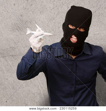 Man wearing robber mask and holding airplane miniature, indoor