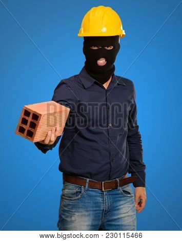 angry criminal man with brick isolated on blue background