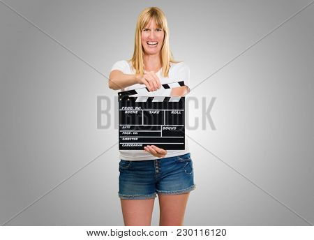 Happy Woman Holding Clapper Board against a grey background