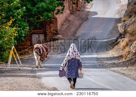 Abyaneh, Iran - October 19, 2016: Iranian Woman Walks On A Road In Abyaneh Village, One Of The Oldes
