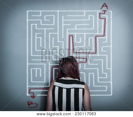 Thoughful Woman Is Considering How To Shorten The Path Through The Maze, Point A To The Point B .