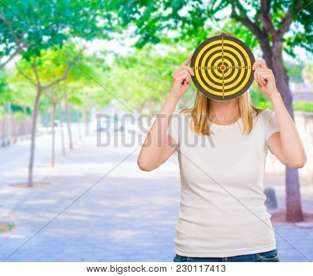 Portrait  Of A Woman Holding Dartboard, Outdoors