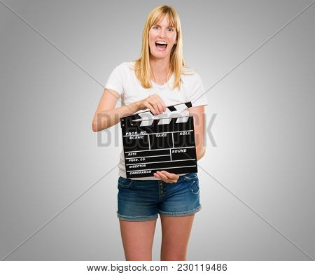 pretty woman holding a clapper board against a grey background