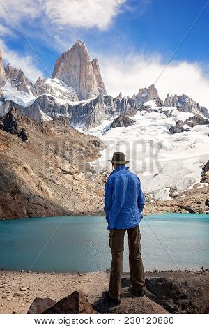 A Man Standing In Front Of Cerro Torre And Laguna De Los Tres In The Patagonis Region Of Argentina