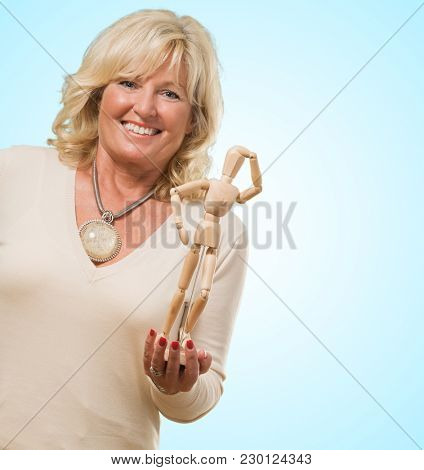 Mature Woman Holding Dummy against a blue background