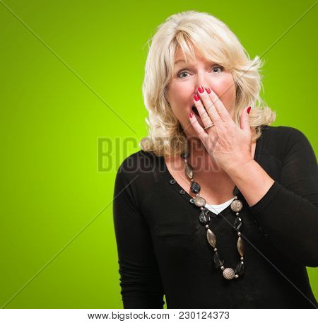 Terrified Woman Covering Her Mouth against a green background