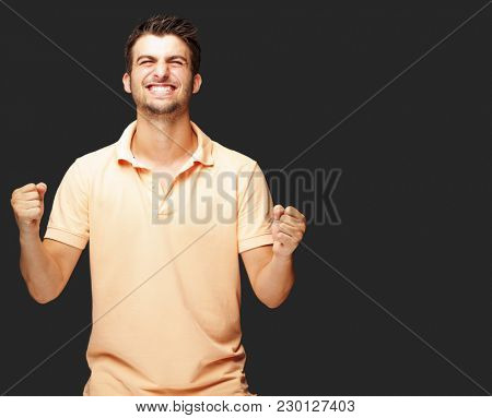 Portrait Of  Smiling Man With The Fists Up Against A Black Background