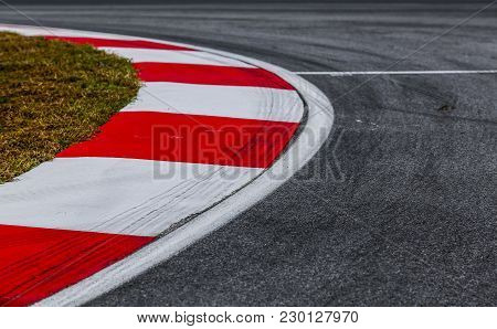 Curving Asphalt Red And White Kerb Of A Race Track Detail