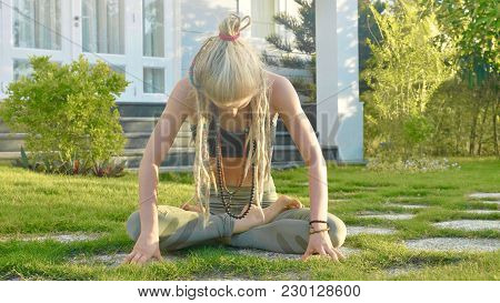 Pranayama Yoga Breath Exercise By A Young Woman In The Backyard Of Her House. Girl Sits On The Lawn