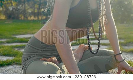 Pranayama Yoga Breath Exercise By A Young Woman In The Backyard Of Her House. Crop Body Of Girl Sits