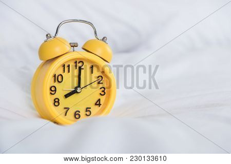 Yellow Alarm Clock At 8 Am On The Bed. To Wake Up